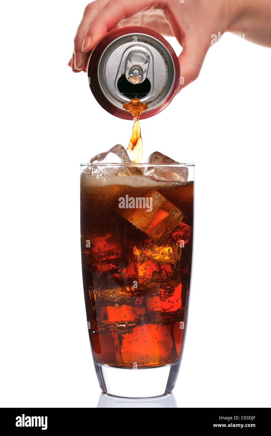Photo of Cola being poured into a glass with ice cubes in, isolated on a white background. - Stock Image
