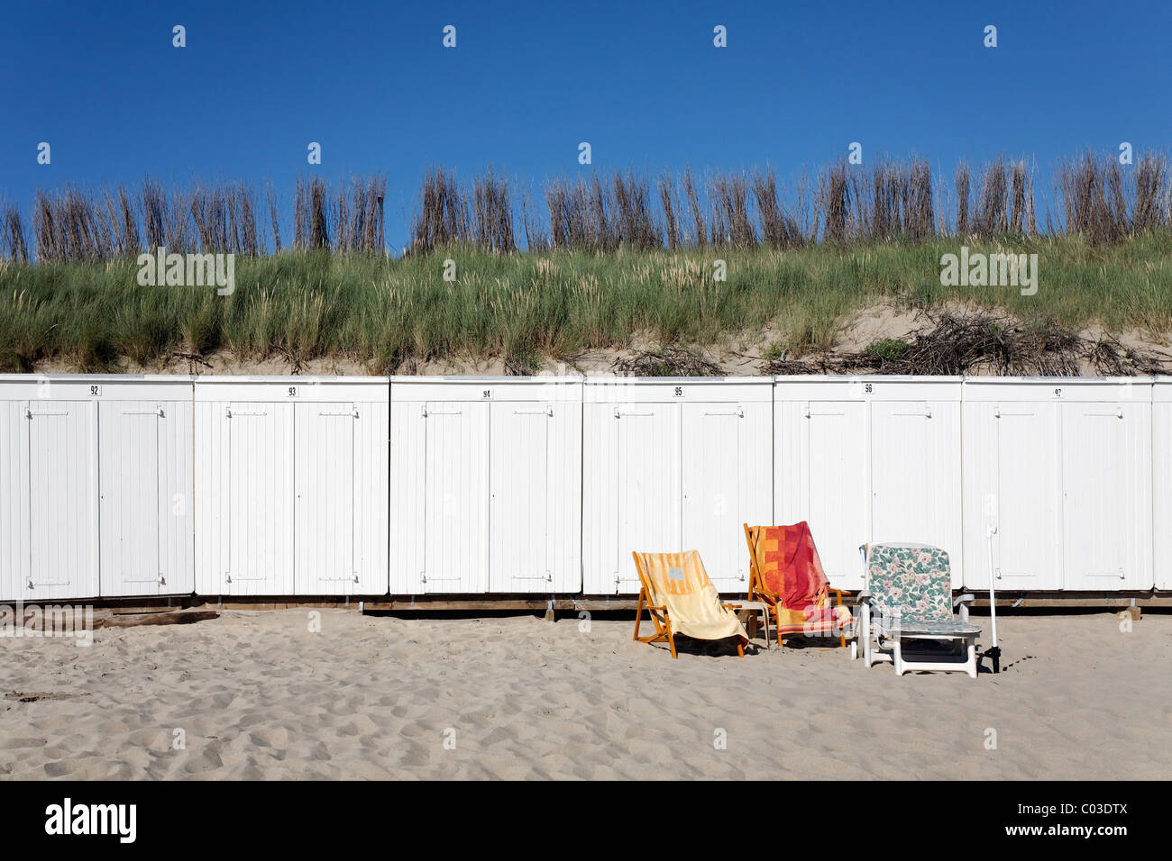Three unoccupied sunbeds with towels in front of white beach huts, , Walcheren peninsula, Zeeland province, Netherlands, - Stock Image