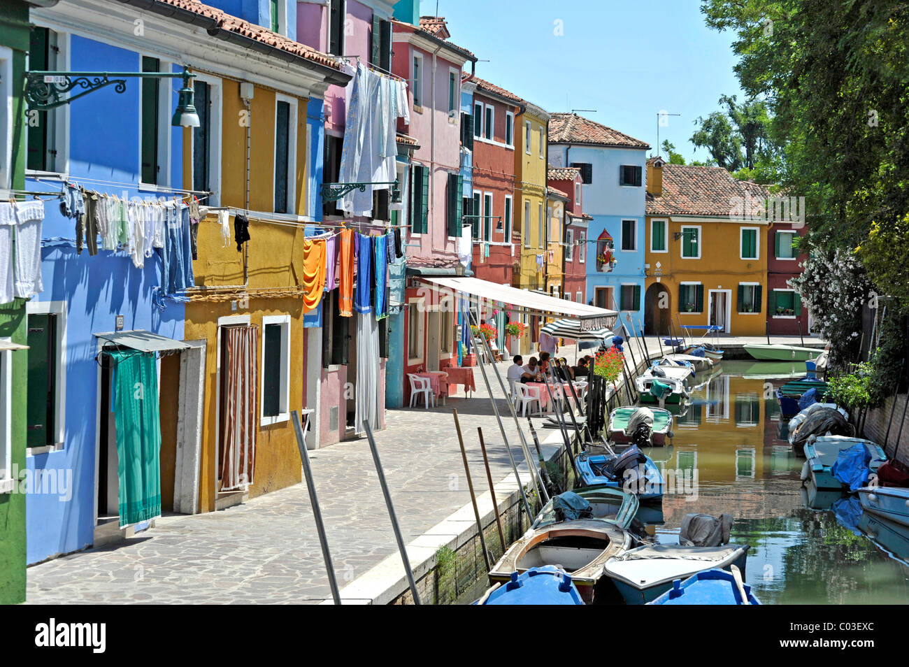 Canal with fishing boats in Burano, a village pub with tourists, fishermen's houses, Burano Island, Venice Lagoon, - Stock Image