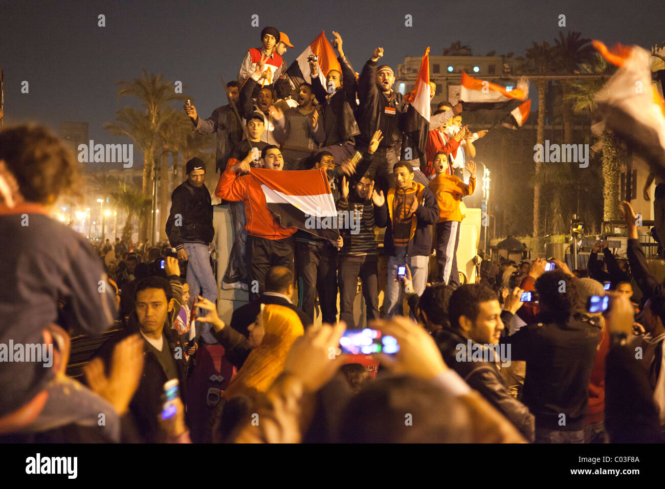 Egyptian demonstrators celebrating victory in the revolution at Tahrir on top of Army truck. - Stock Image