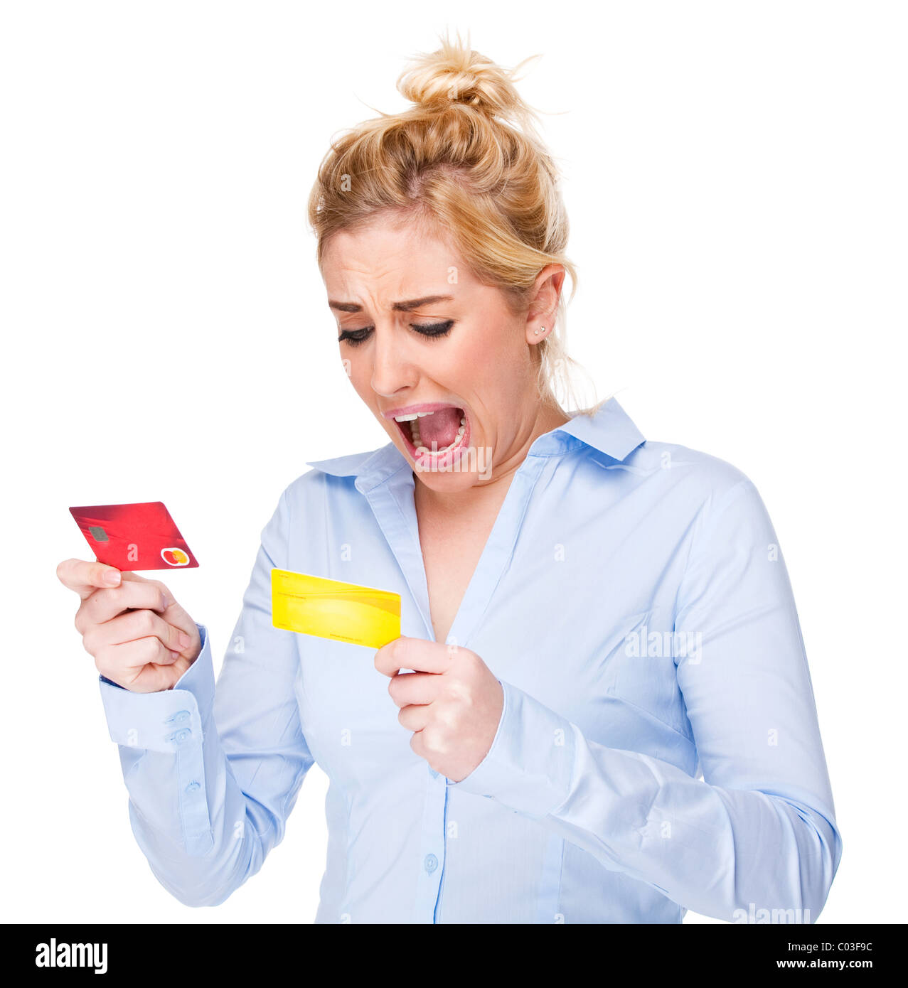 Attractive young woman with money worries - shocked by credit cards - Stock Image