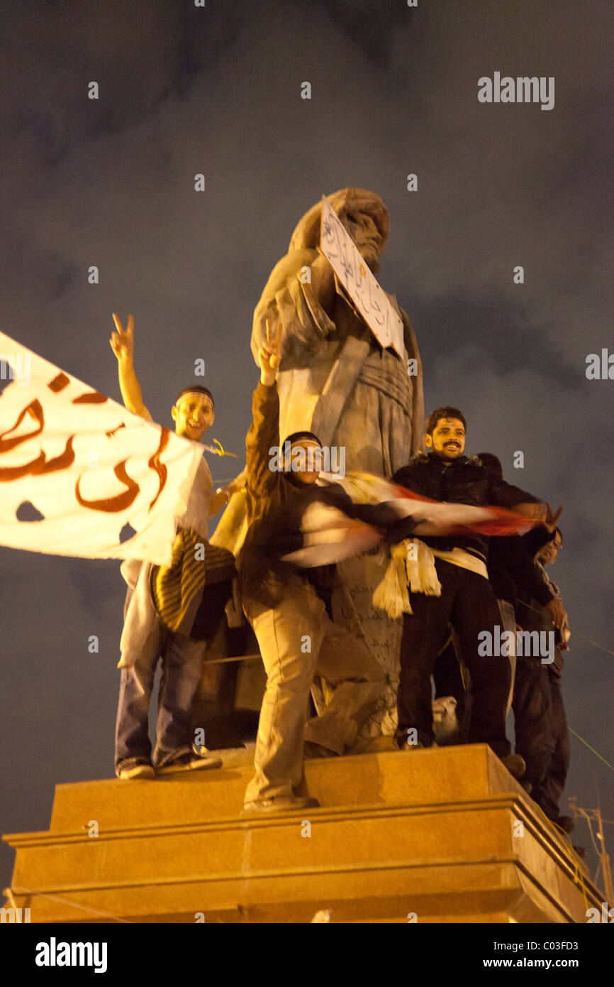Egyptian demonstrators celebrating victory in the revolution at Tahrir on top of statue of Omar Makram - Stock Image