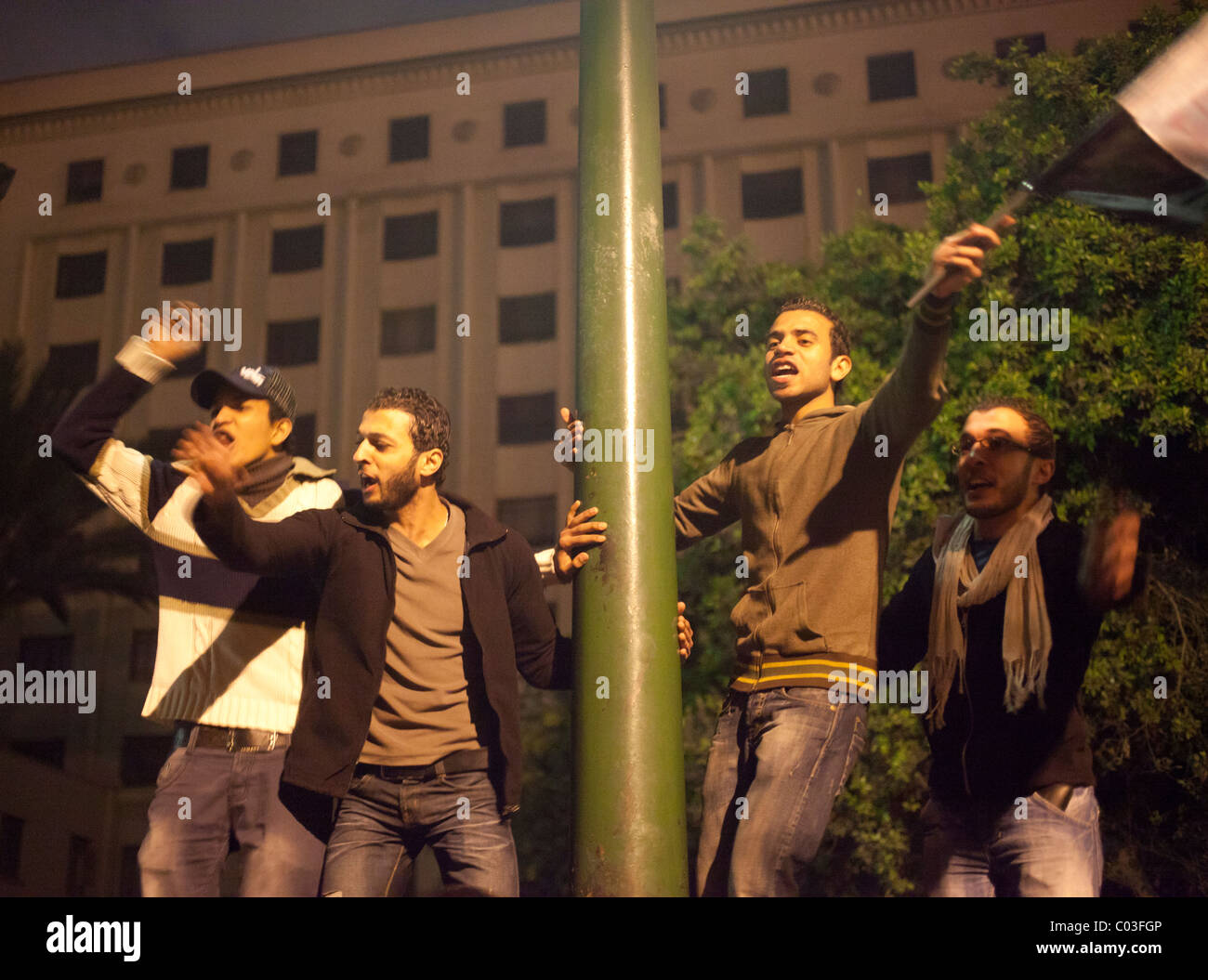 Egyptian demonstrators celebrating victory in the revolution at Tahrir on top of fence - Stock Image