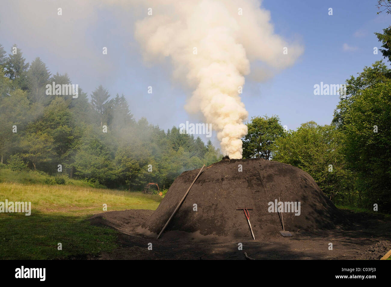 Smoking charcoal kiln, Walpersdorf, Kreis Siegen-Wittgenstein district, North Rhine-Westphalia, Germany, Europe - Stock Image