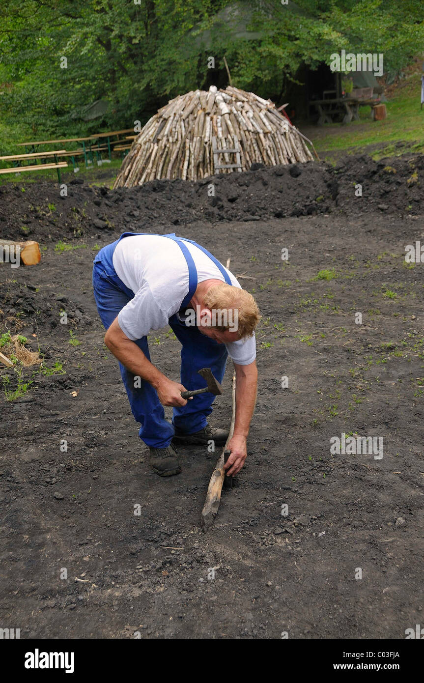 Charburner using a stick to draw a circle for a new charcoal kilns, Walpersdorf, Kreis Siegen-Wittgenstein district - Stock Image