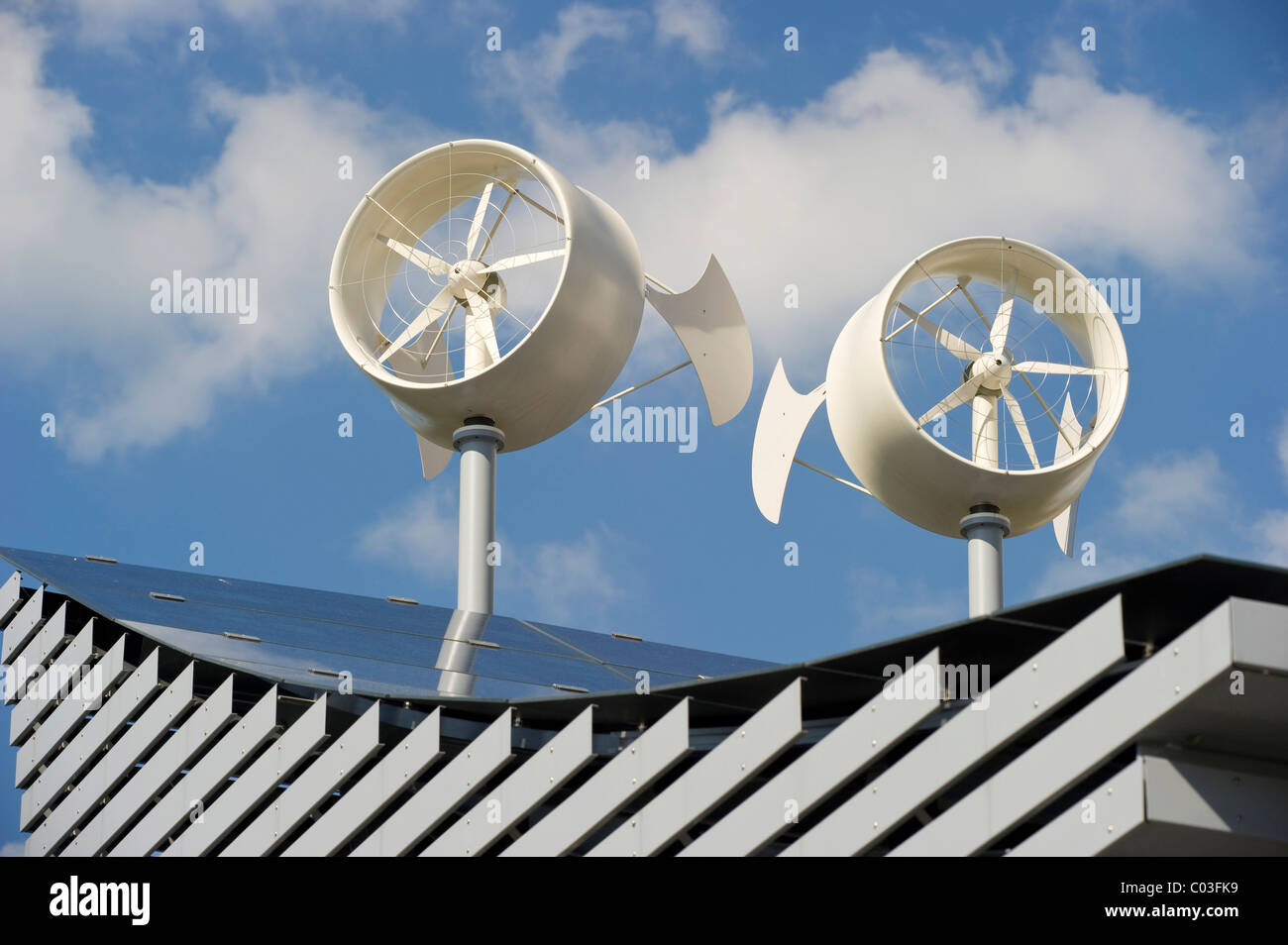 Solar panels and mini wind turbines on the roof of a hotel in Freiburg, Breisgau region, Baden-Wuerttemberg - Stock Image