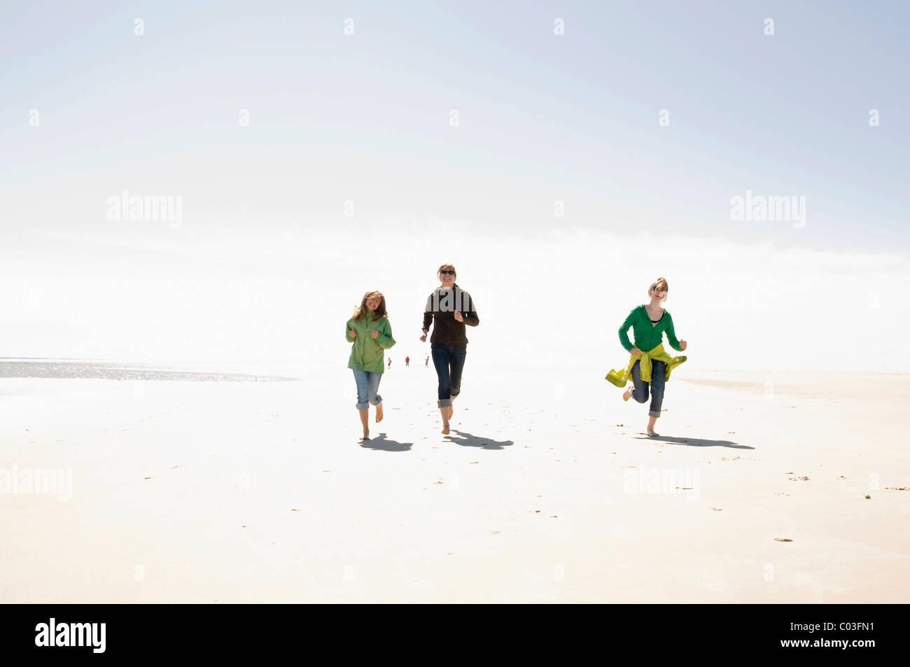 Woman and two children running on the beach of Amrum island, Schleswig-Holstein, Germany, Europe - Stock Image