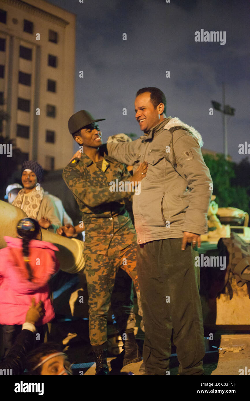 Egyptian civilian and army soldier embracing on top of tank, Tahrir Square, Cairo, Egypt - Stock Image