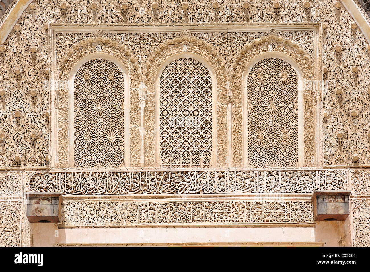 Elaborate stucco ornaments, arabesques and Koranic verses made of plaster at the Medersa Bou Inania Koran School, - Stock Image