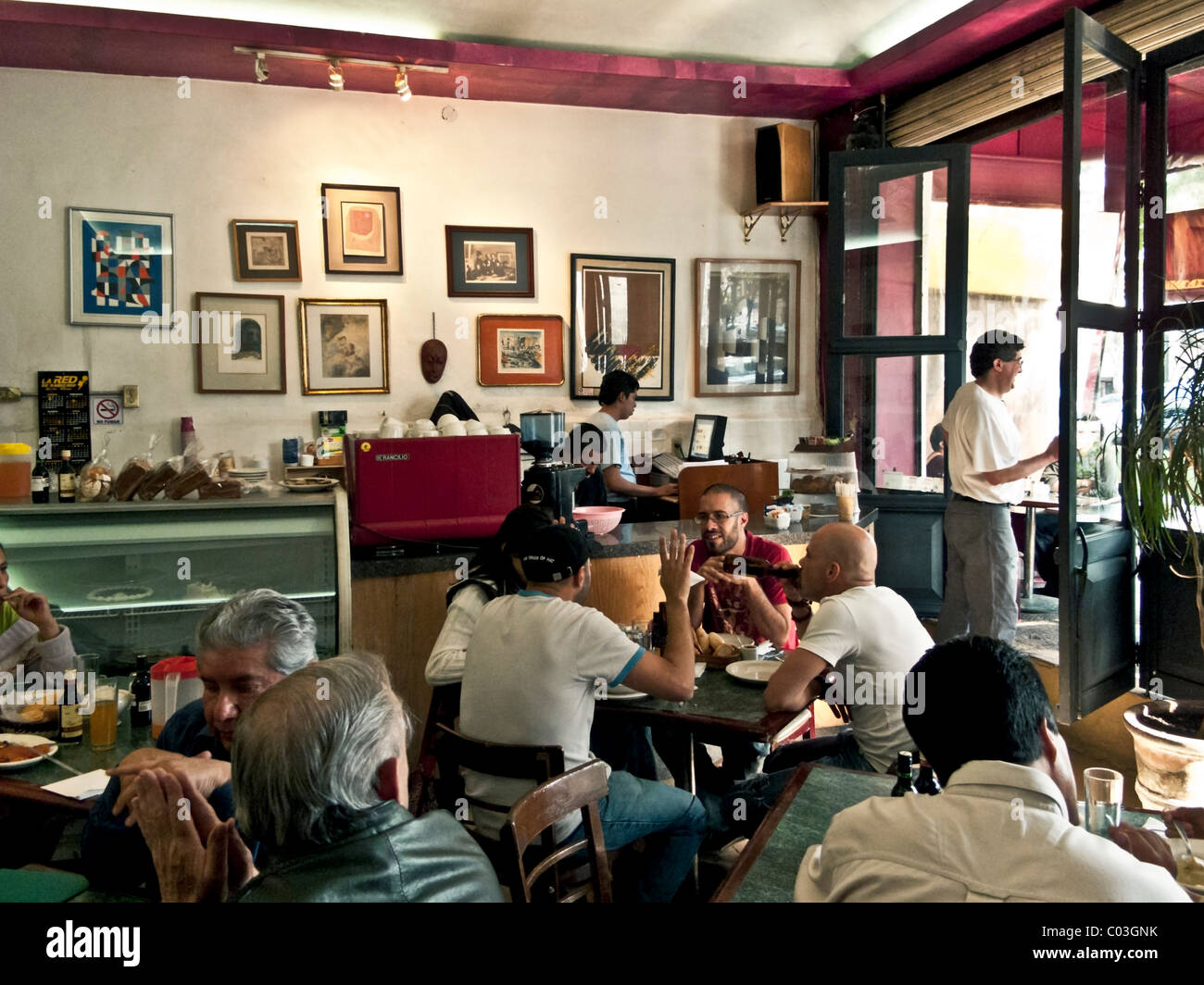 light filled interior of charming crowded art filled cafe with old world ambiance & conviviality Roma District - Stock Image