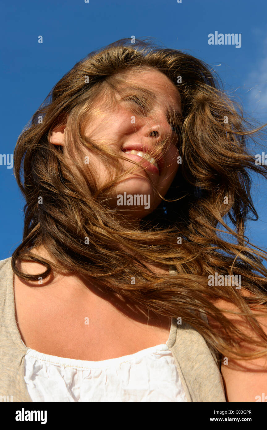 Young woman looking upward, her hair tousled by the wind, Finistere departement, Brittany region, France, Europe - Stock Image