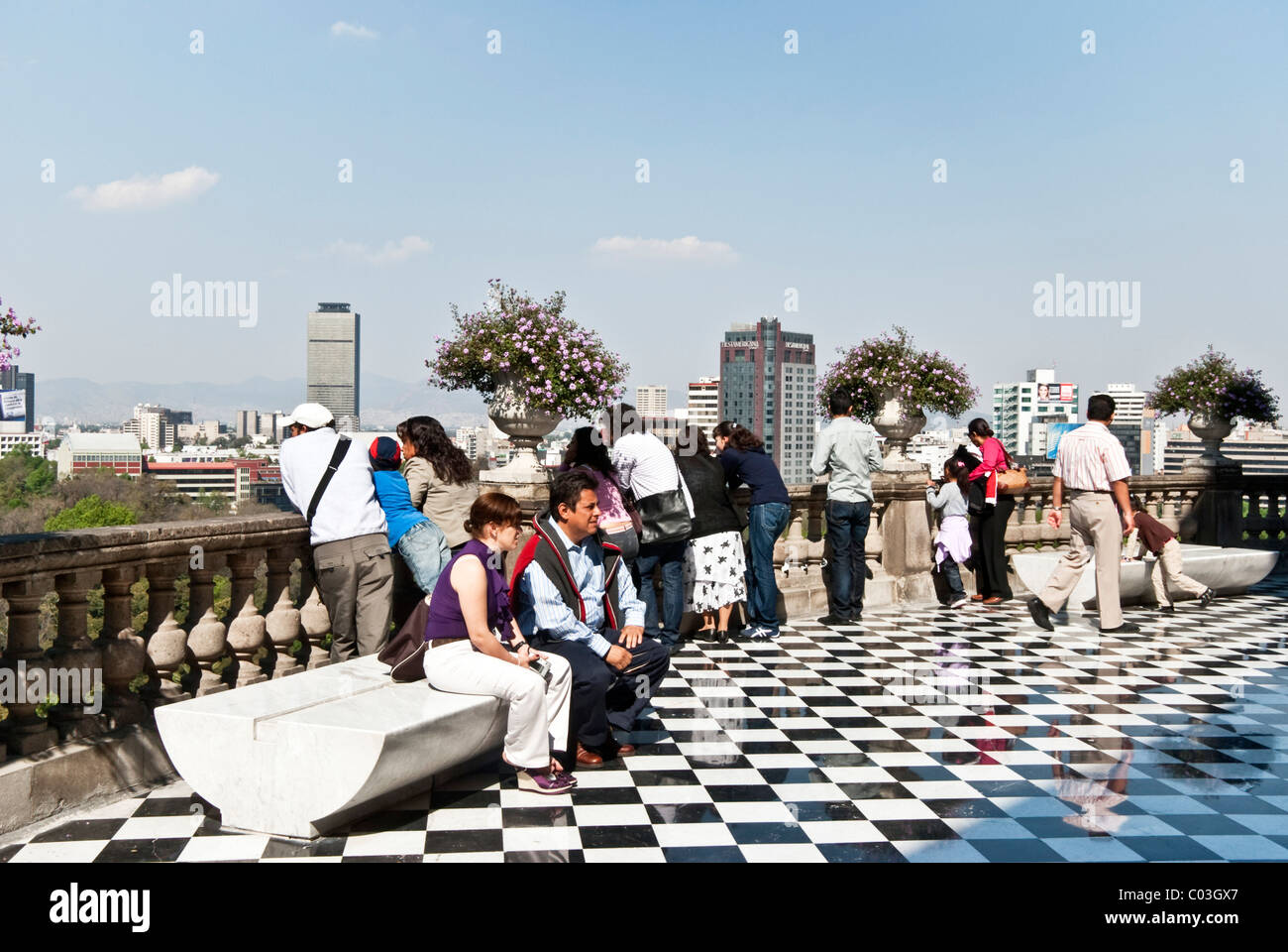 visitors to terrace of Chapultepec Castle enjoy magnificent view of modern Mexico City skyline & encircling - Stock Image