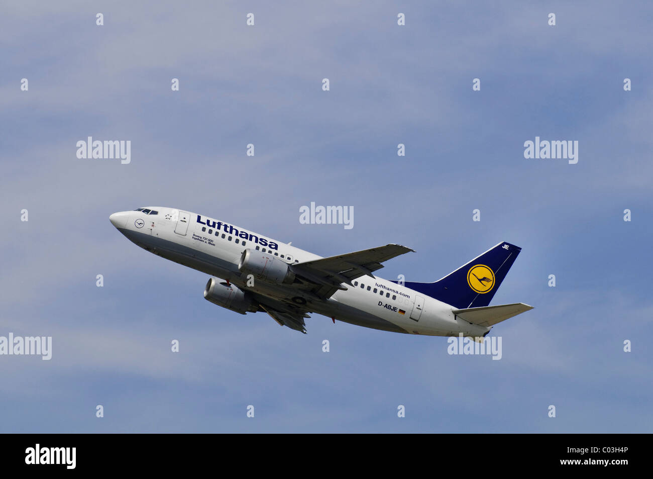 Boeing 737-500 airline from Lufthansa climbing in front of cirrostratus clouds - Stock Image