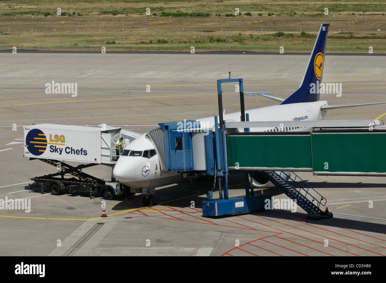 Lufthansa plane being unloaded, container and gangway connected to the airplane, apron, Cologne Bonn Airport - Stock Image