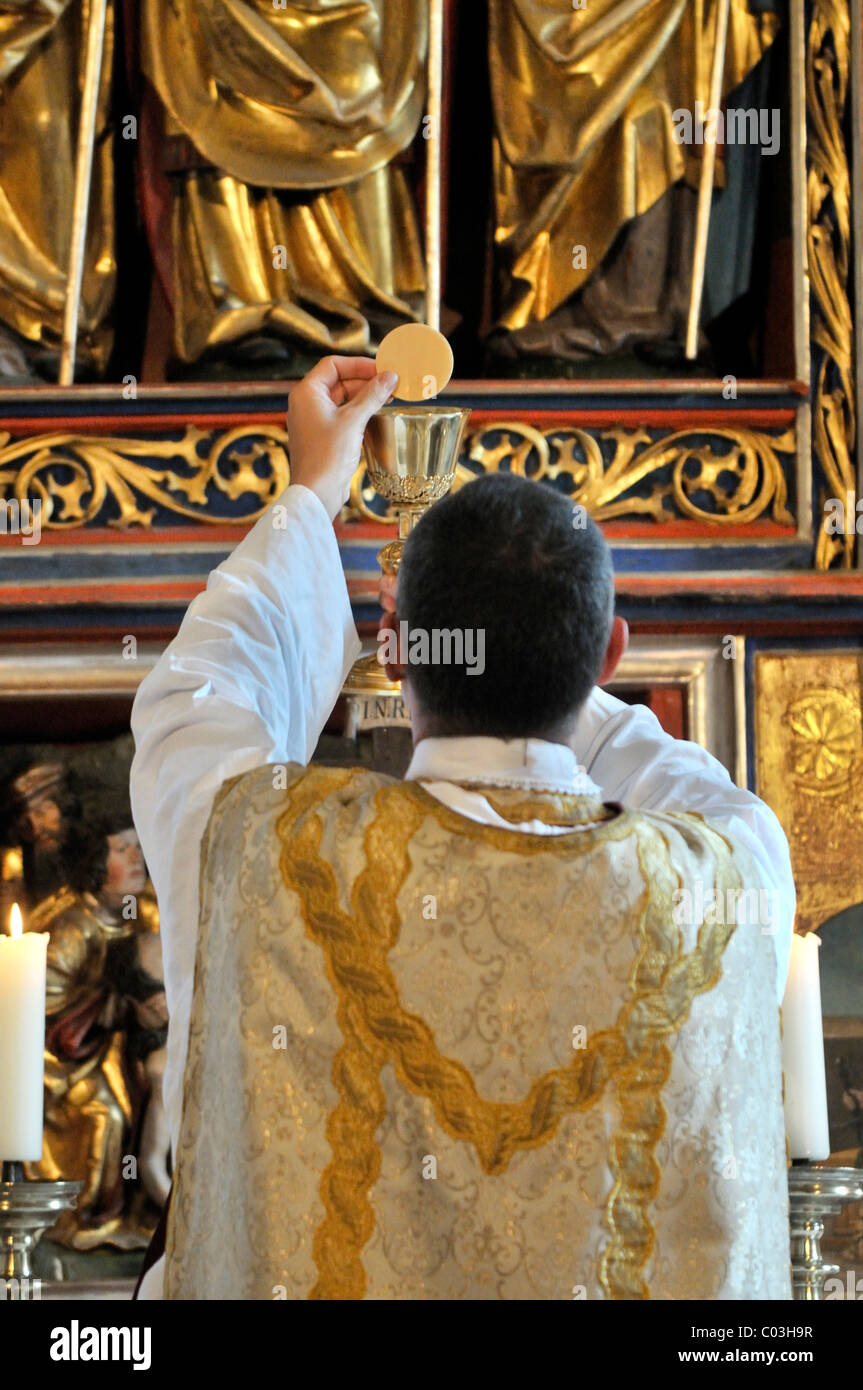 Catholic priest with a chalice and host at the Communion ...