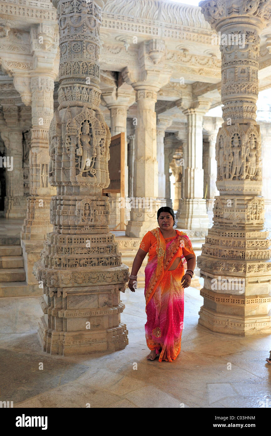 Indian woman wearing a traditional sari in the inner hall with ornate marble pillars in the Temple of Ranakpur - Stock Image