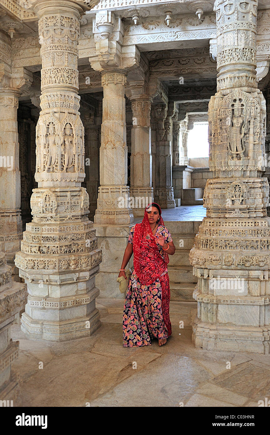 Young Indian woman wearing a traditional sari in the inner hall with ornate marble pillars in the Temple of Ranakpur - Stock Image