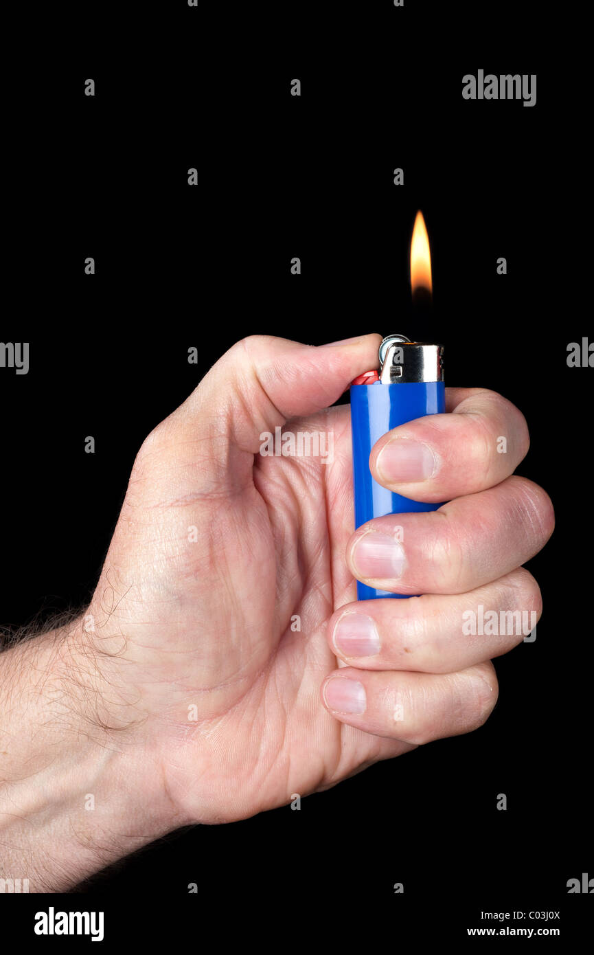 Image of a person lighting a blue portable butane lighter against a dark background. - Stock Image