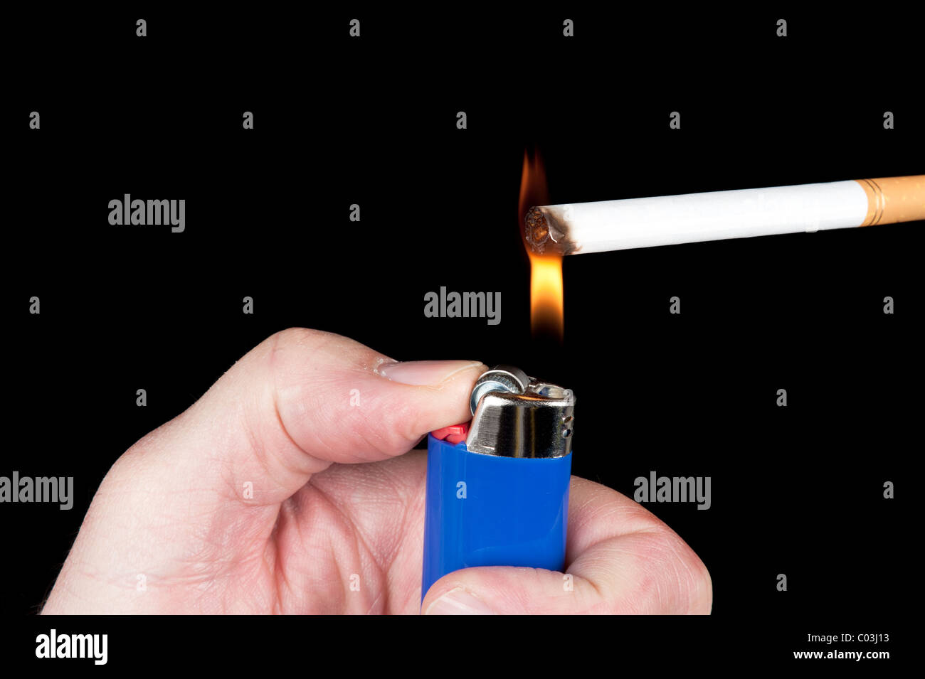 A person lights a cigarette with a blue butane lighter. - Stock Image
