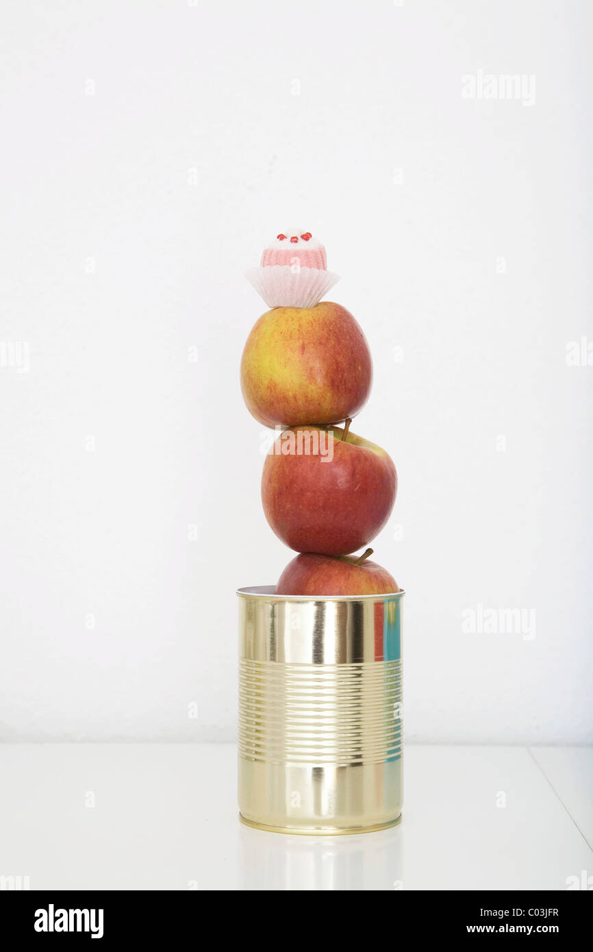 Apples and a chocolate in a tin can, preserved food - Stock Image