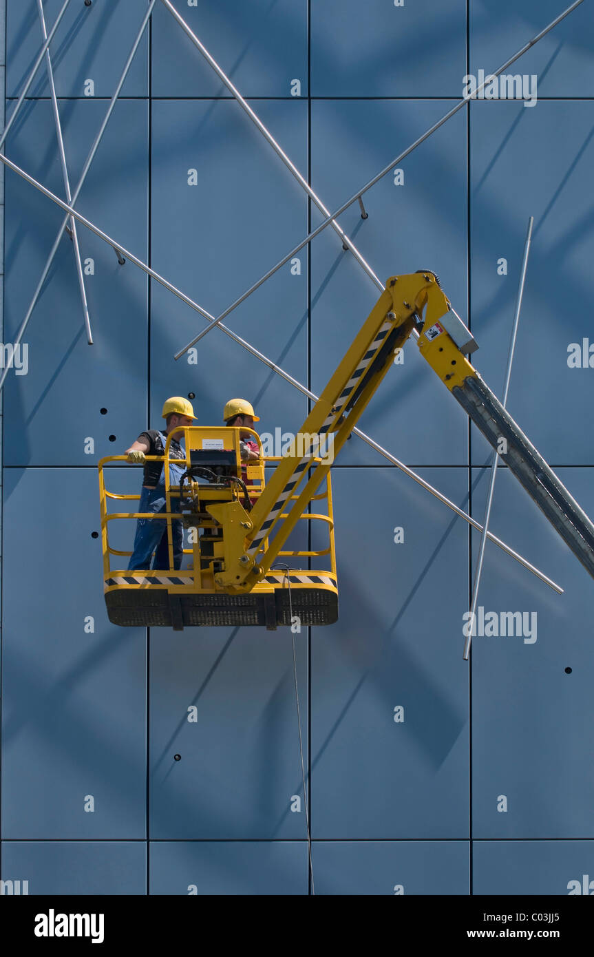 Workers wearing hard hats, standing on an articulated telescoping