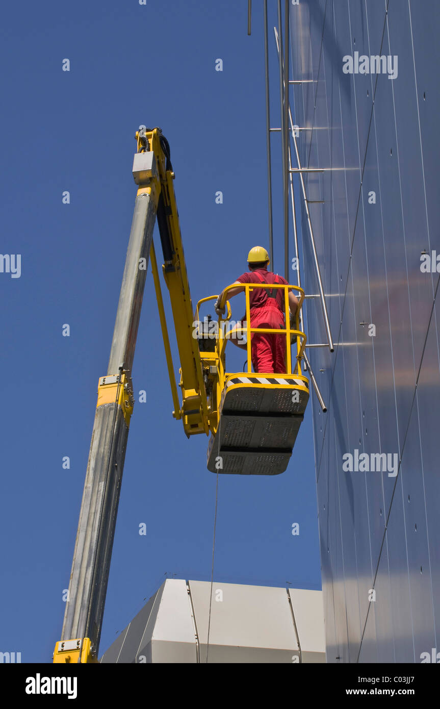 Worker wearing hard hat standing on an articulated telescoping boom