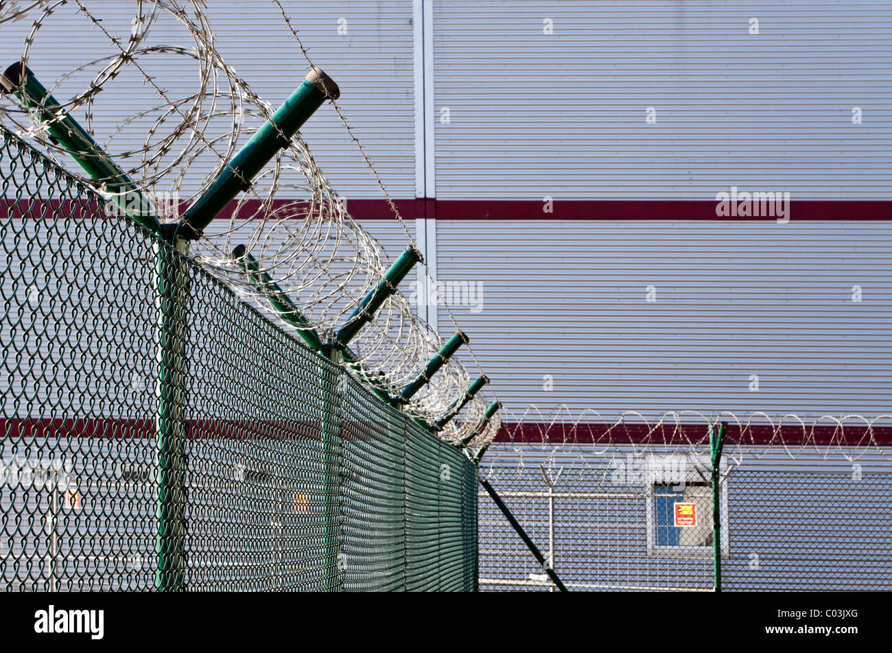 Barbed wire fence in front of a warehouse - Stock Image