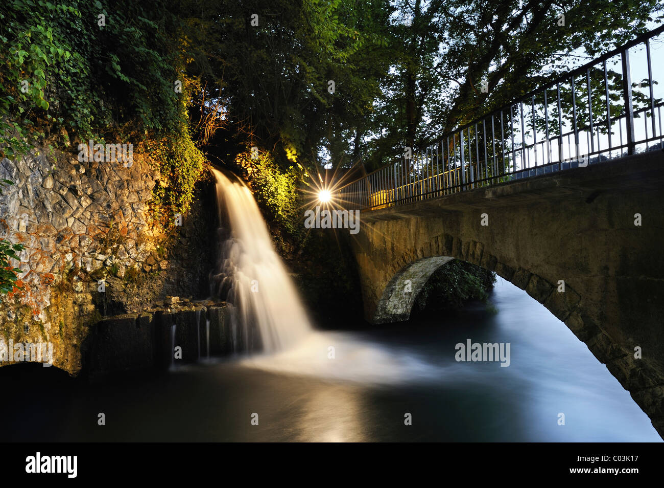 Small illuminated waterfall at the outflow channel of the power station below the mill and next to the Rheinfall - Stock Image