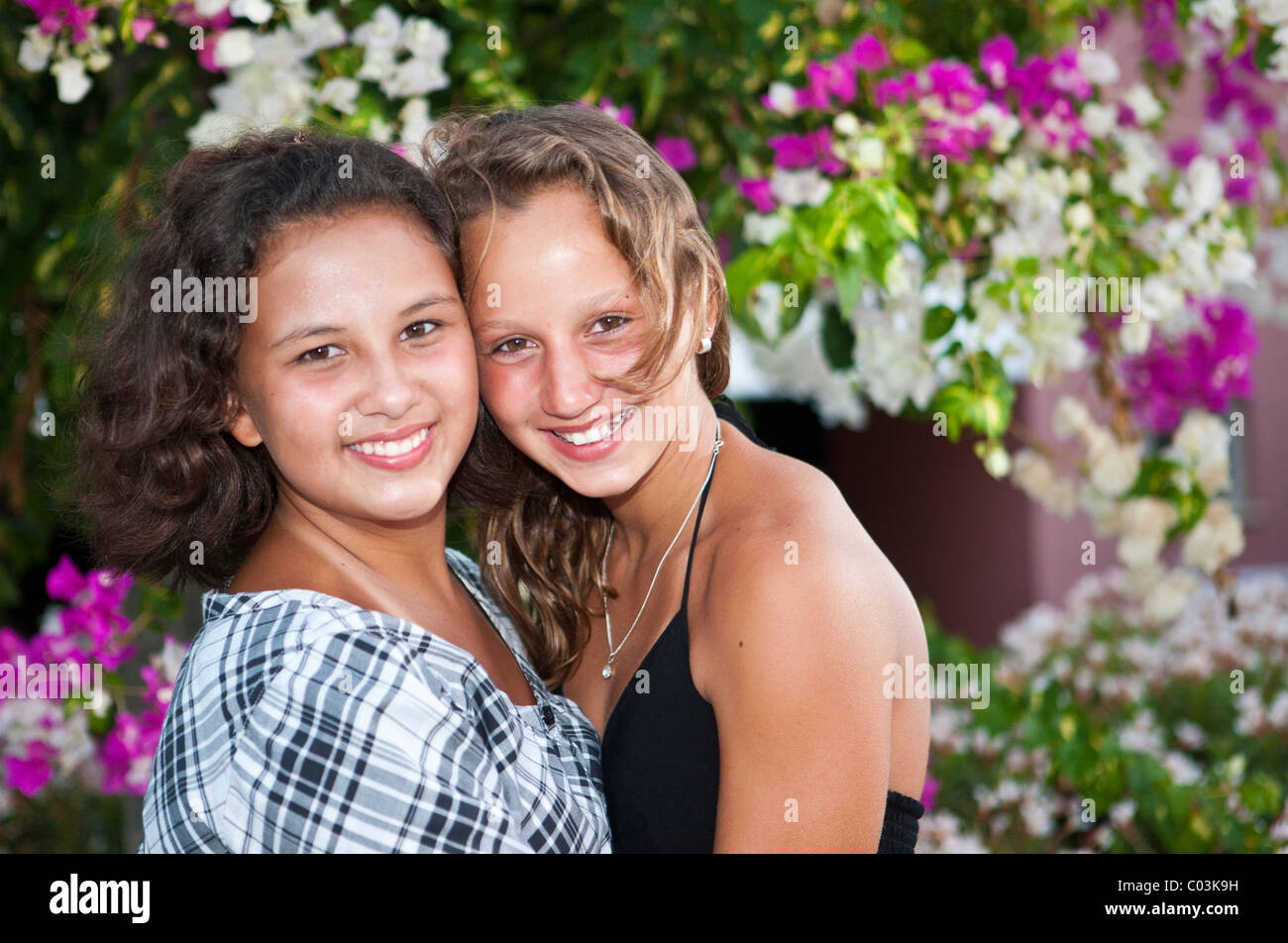 Portrait of two thirteen-year-olds girls in front of flowers - Stock Image