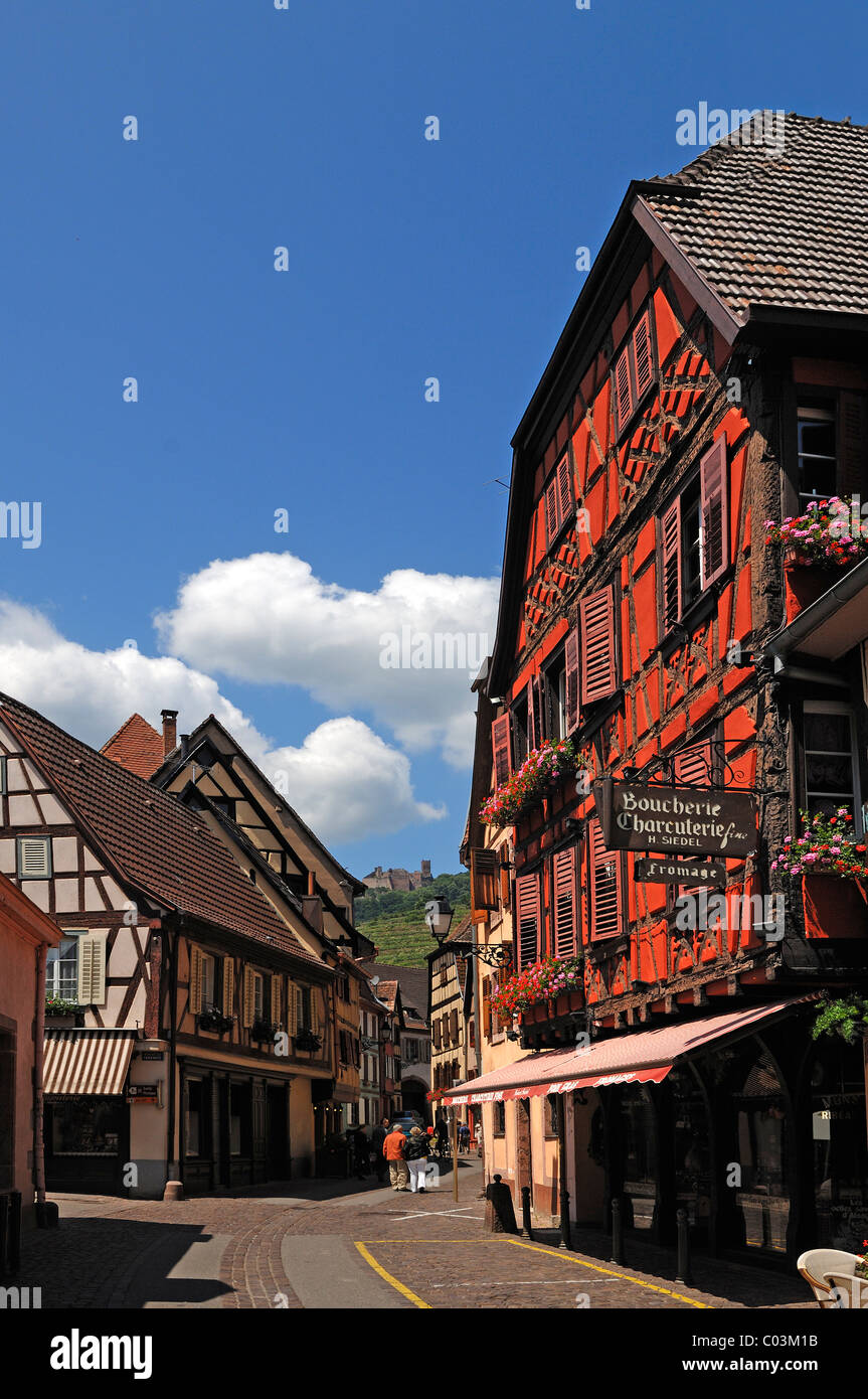 Main street with old Alsatian half-timbered houses, in the distance, the ruins of Ulrichsburg Castle, Grand'Rue, - Stock Image