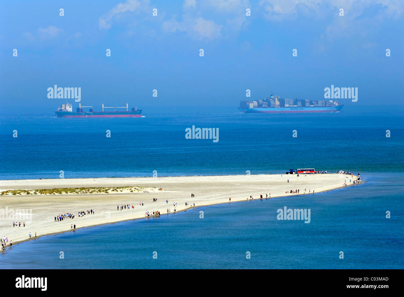 Headland with people where the North Sea and the Baltic Sea meet, container ships at back, Skagen, Jutland, Denmark, - Stock Image