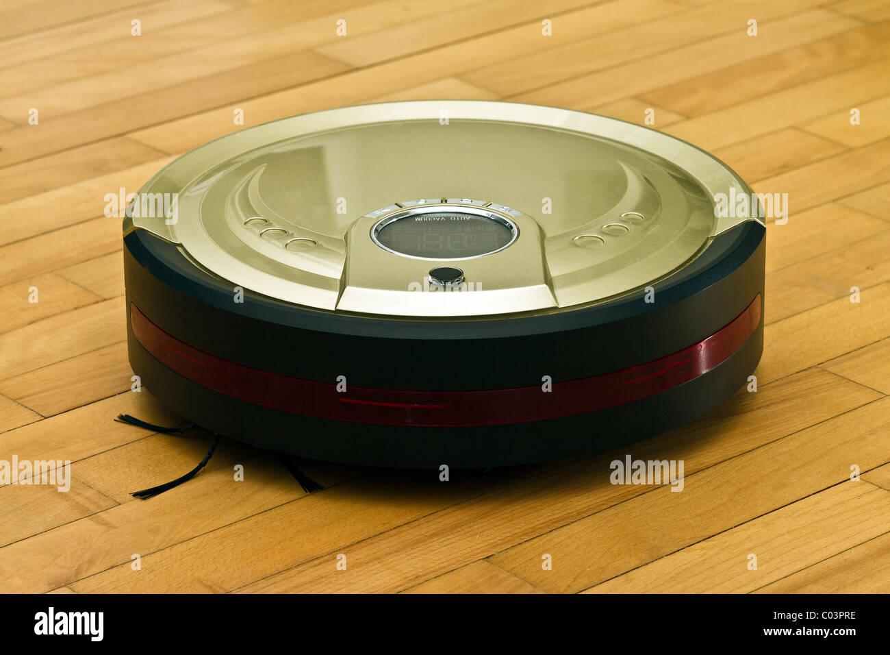 A robotic vacuum cleaner on parquet - Stock Image