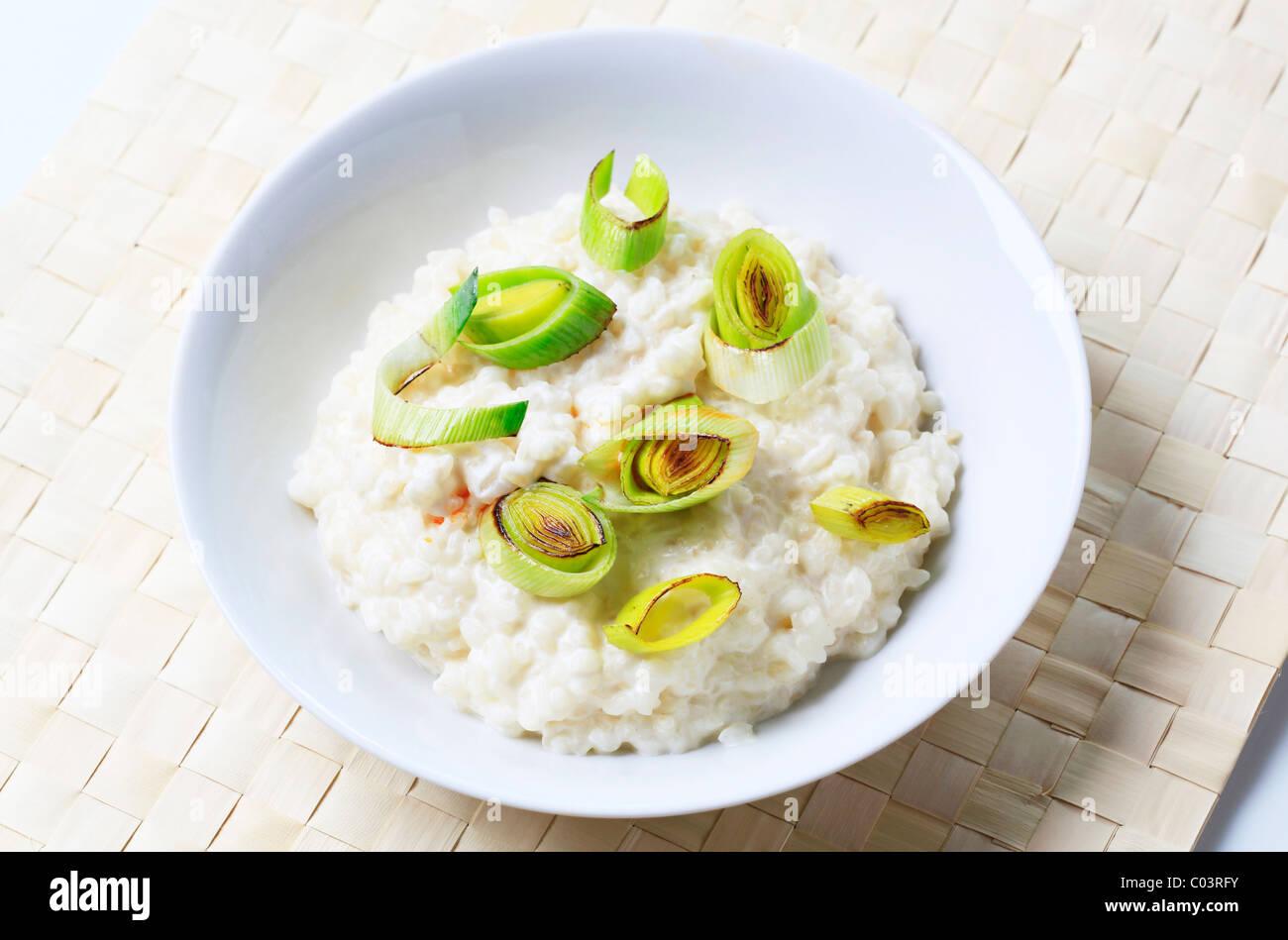 Bowl of rice pudding with leek - closeup - Stock Image