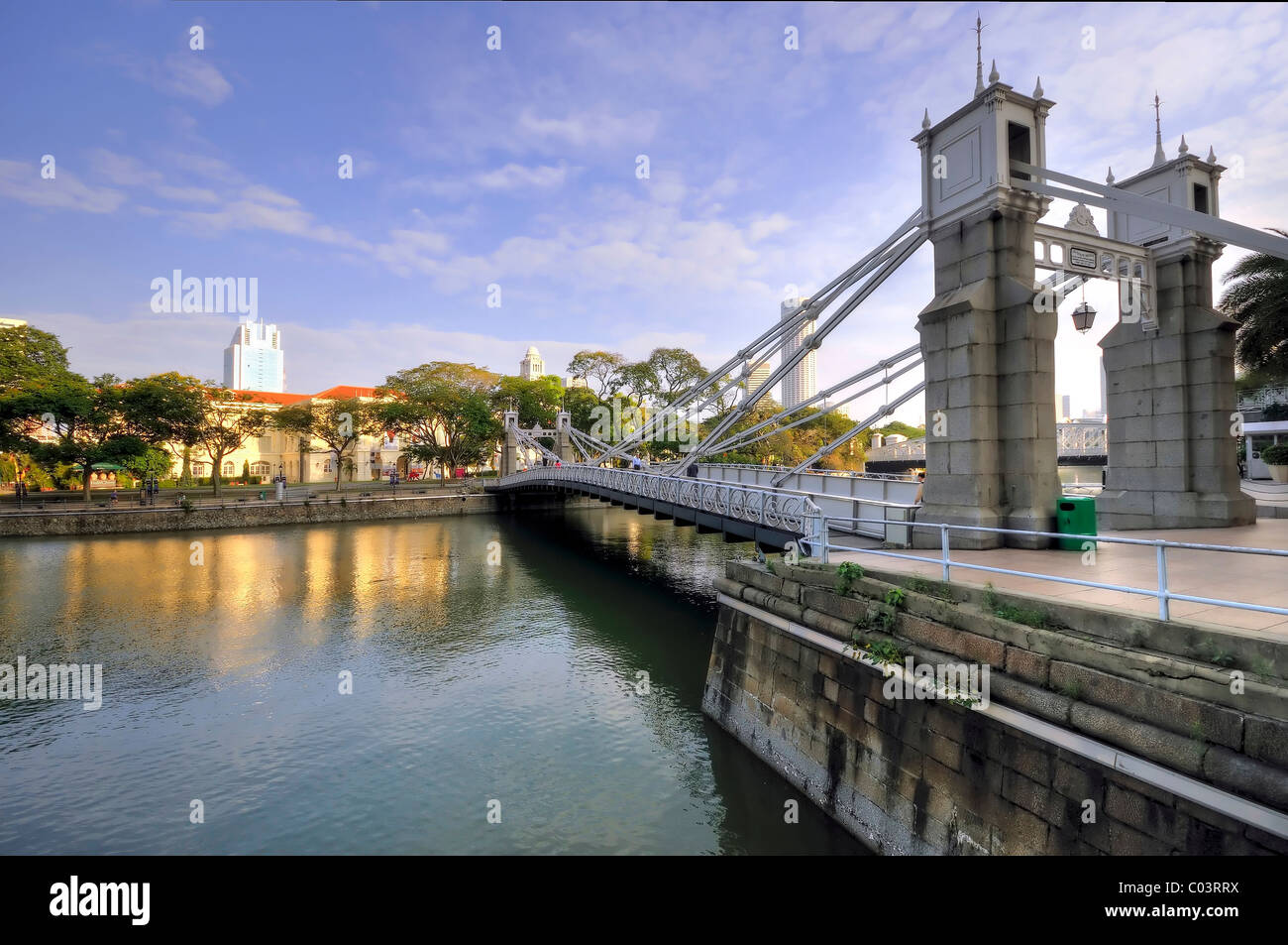 The historic Cavenagh Bridge spanning the Singapore River and overlooking the Singapore City Hall skyline. - Stock Image