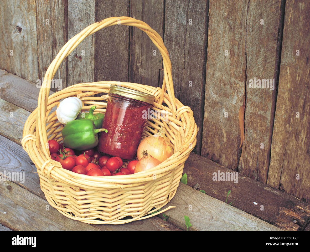 Basket of freshly picked organic vegetables and a jar of homemade salsa on a rustic background. Stock Photo