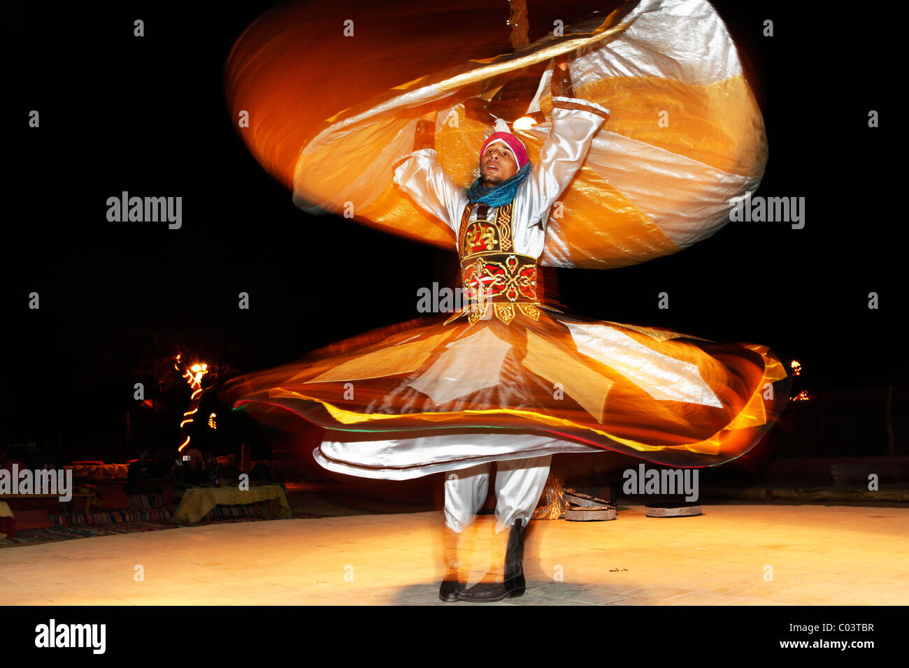 A Whirling Dervish dances to entertain tourists in Egypt. - Stock Image