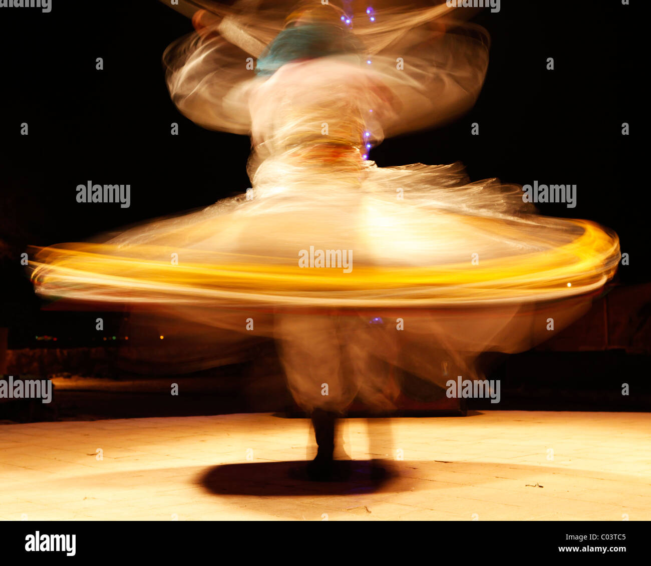A Whirling Dervish dances to entertain tourists in Egypt. Whirling Dervishes are members of a Sufi order. - Stock Image