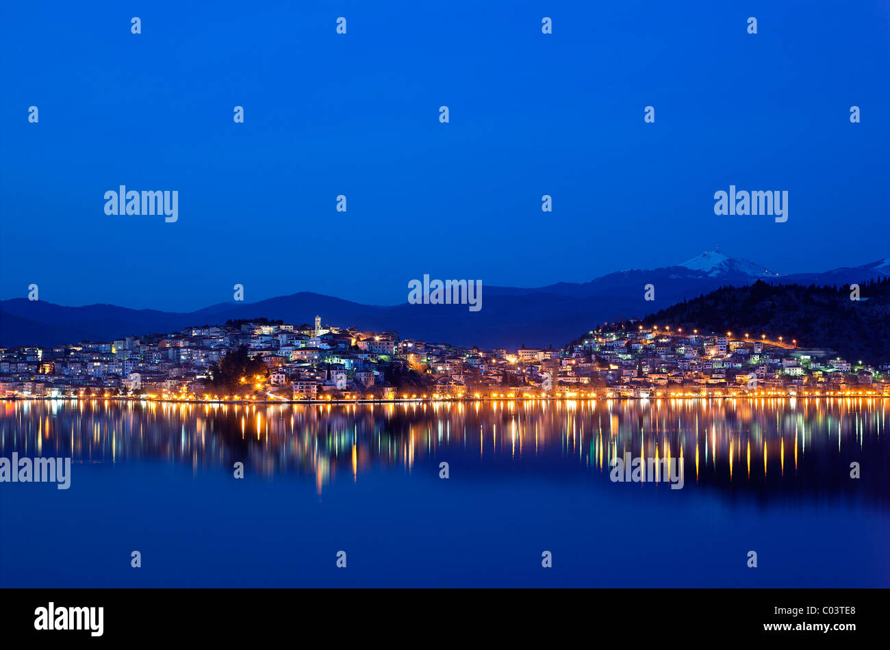 Kastoria town in the 'blue' hour, reflected in the beautiful 'Orestias' or 'Orestiada' lake. - Stock Image