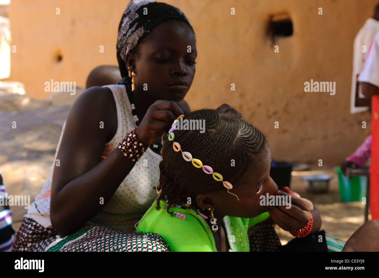 Teenage girls adorning each others hair for the Muslim festival of Tabaski. Dogon Country, Mali - Stock Image