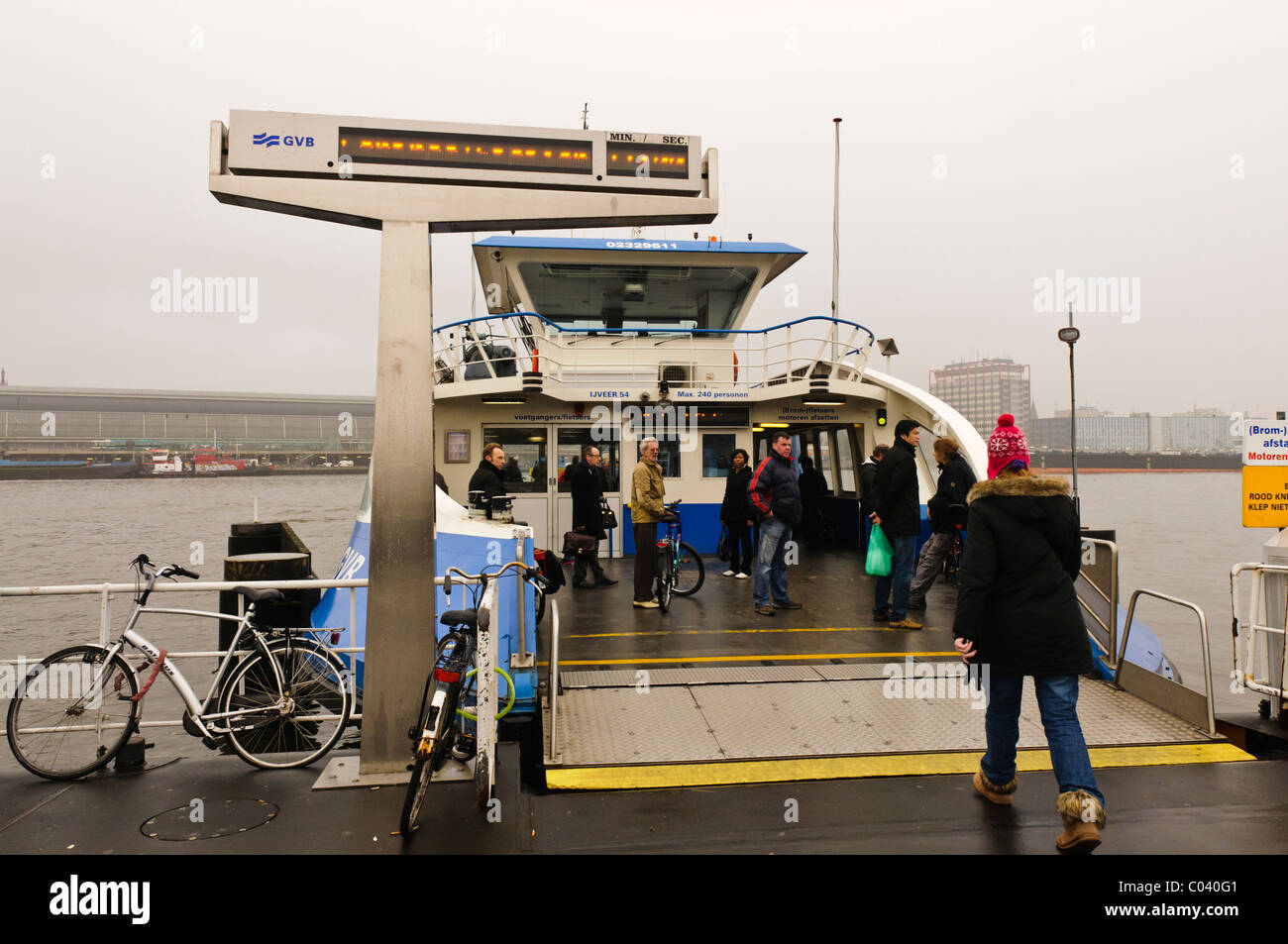 Passengers boarding the GVB passenger and bike ferry crossing the Het Ij, Amsterdam in poor weather with low visibility - Stock Image