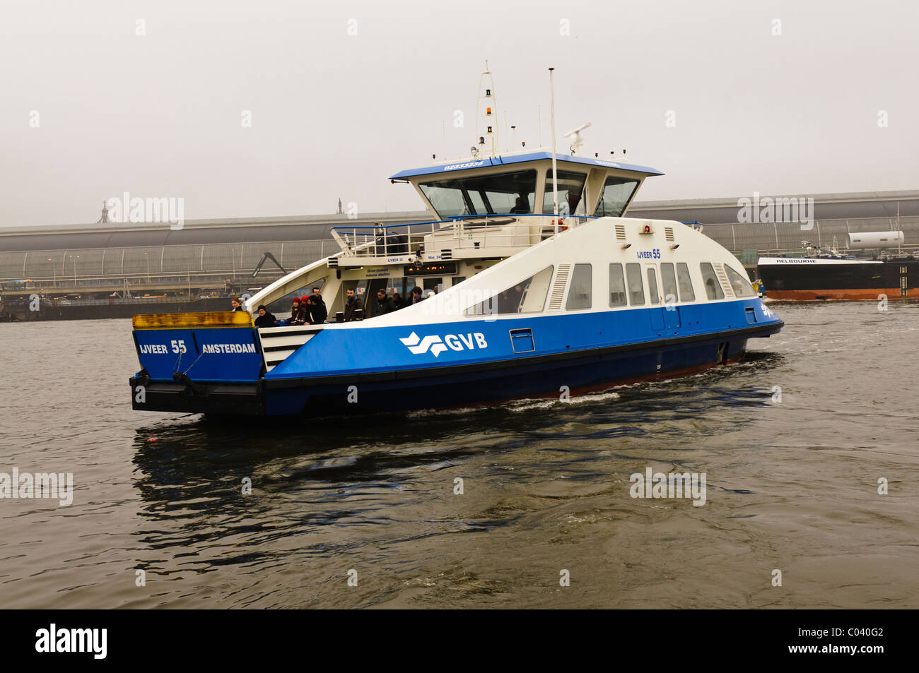 GVB passenger and bike ferry crossing the Het Ij, Amsterdam in poor weather with low visibility - Stock Image