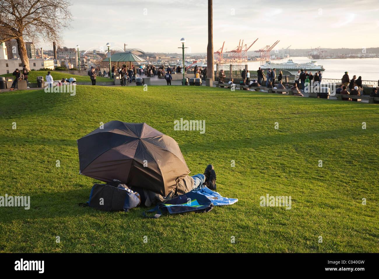 Man sleeping under an umbrella - Seattle, Washington - Stock Image