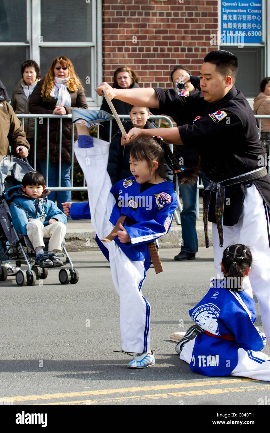 Young female Tae Kwan Do student breaks a board with her foot during