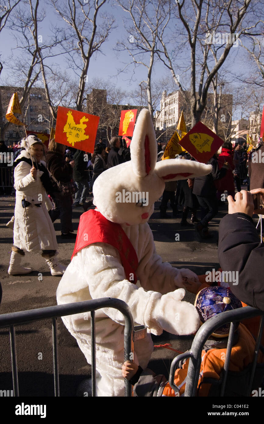 White Rabbit with red sash greeting children in New York City's 2011 Chinese New Year Parade (Year of the Rabbit) - Stock Image