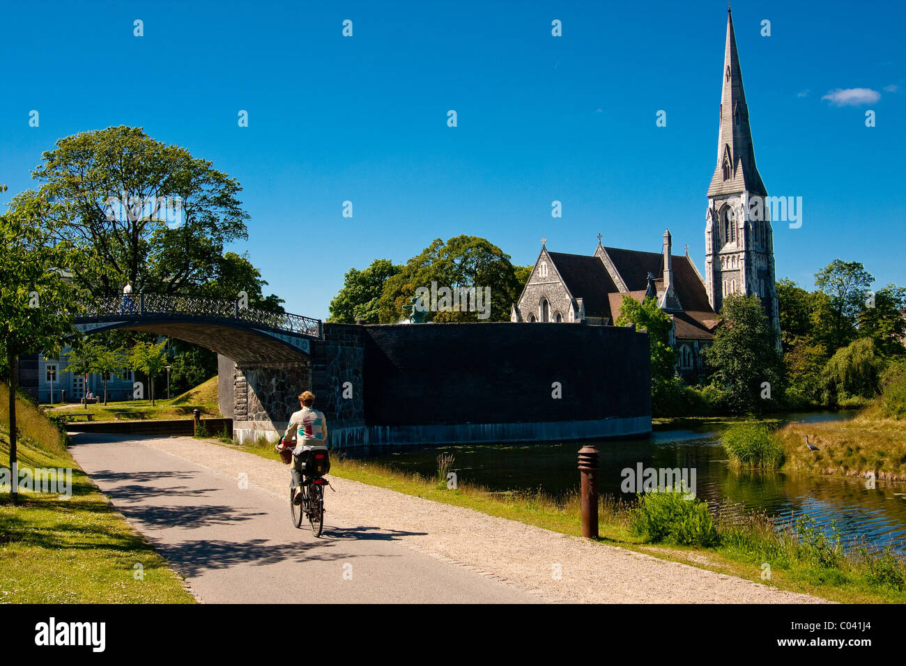 Bicyclist riding on a path near Saint Albans Anglican Church in Copenhagen, Denmark. - Stock Image