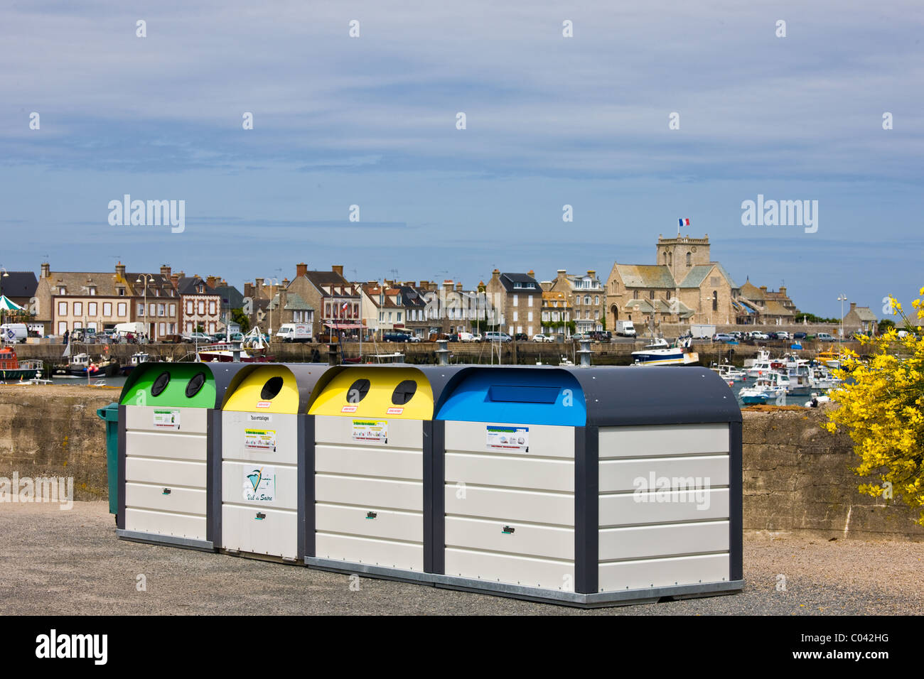 Large plastic recycling bins, dechetterie, for plastic, paper, glass spoil the view in Barfleur in Normandy, France Stock Photo