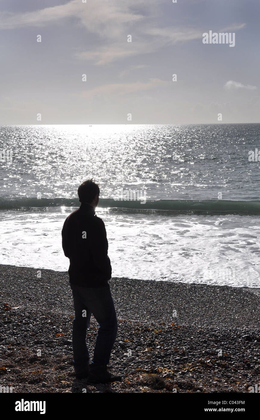 A young man stood on the beach looking out over a sun drenched sea - Stock Image