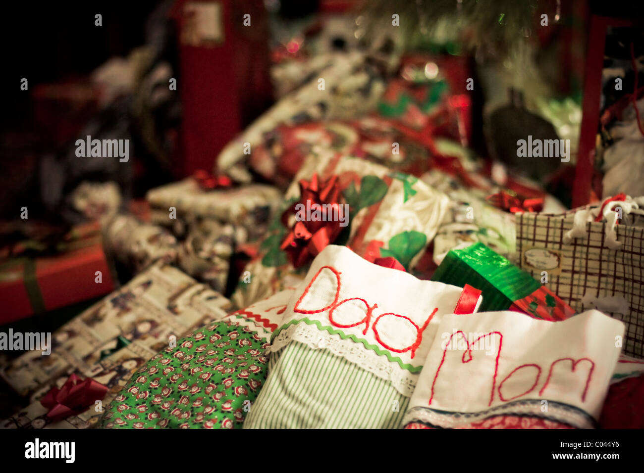 A Pile Of Wrapped Christmas Gifts And Stuffed Hand Embroidered Stockings Under The Tree