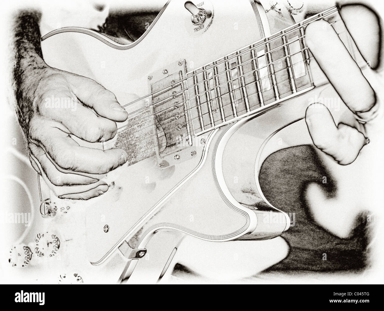 Closeup of a guitarist playing an electric guitar with solarised black and white effect - Stock Image