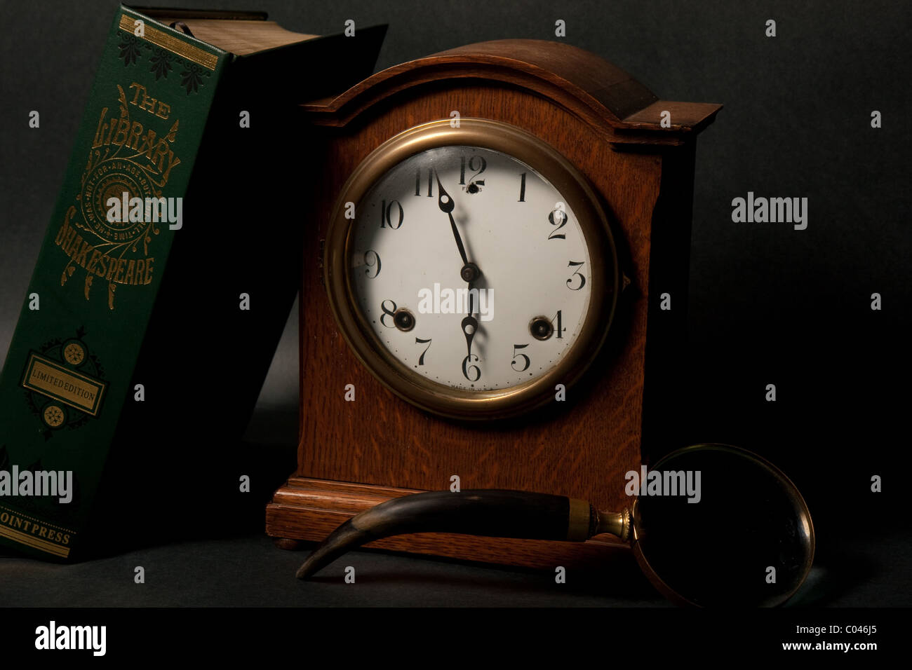 A seth thomes clock and a limited edition Shakespere leather back book, with a black backdrop - Stock Image